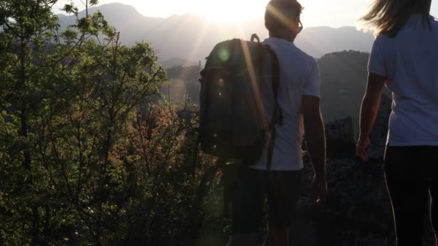 Hiking couple pause above valley and mountains at sunrise