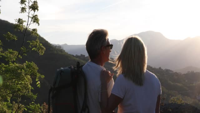 hiking couple pause above valley and mountains at sunrise - mature couple stock videos & royalty-free footage