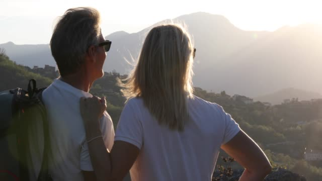 hiking couple pause above valley and mountains at sunrise - blonde hair stock videos & royalty-free footage