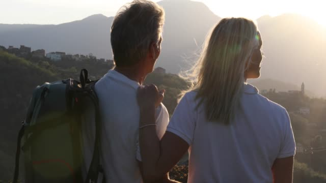hiking couple pause above valley and mountains at sunrise - coppia di età matura video stock e b–roll