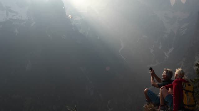 hiking couple pause at edge of precipice, looking off - coppia di età matura video stock e b–roll