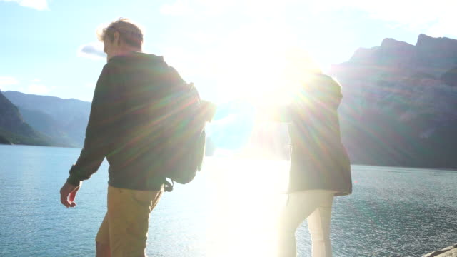 Hiking couple pause at mountain lake to enjoy sunrise