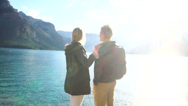 vidéos et rushes de hiking couple pause at mountain lake to enjoy sunrise - personal perspective