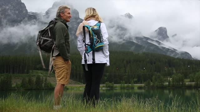 hiking couple pause by mountain lakeshore, skip stones - eskapismus stock-videos und b-roll-filmmaterial