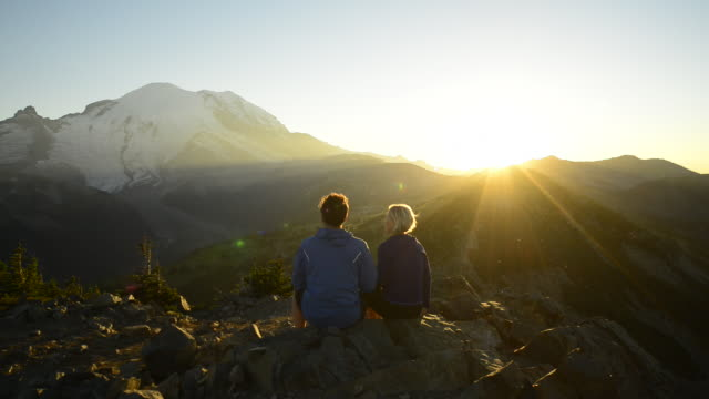 hiking couple pause to enjoy the sunrise together - mt rainier stock videos & royalty-free footage