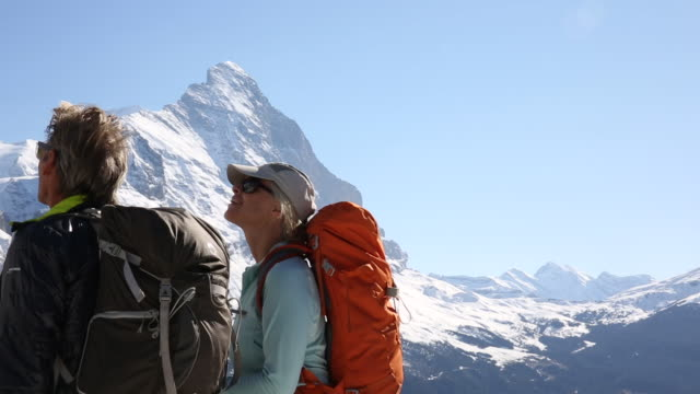 hiking couple pause to enjoy view below snow capped mountains - top garment stock videos and b-roll footage