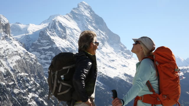 Hiking couple pause to enjoy view below snow capped mountains