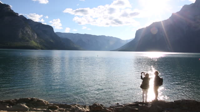 Hiking couple pause to take pic across mountain lake