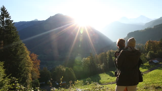 Hiking couple pause to watch sunrise over mountains