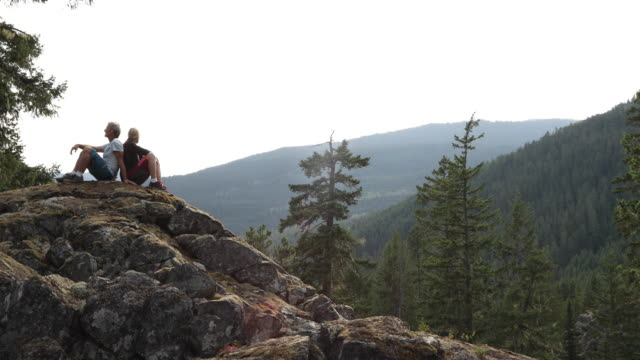 wanderpaar entspannen bei sonnenaufgang über bewaldeten hügeln - sitzen stock-videos und b-roll-filmmaterial
