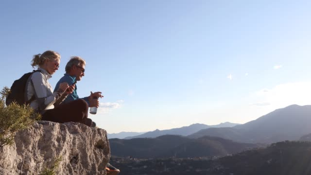 hiking couple relax on cliff edge, she takes smart phone pic - mature couple stock videos & royalty-free footage