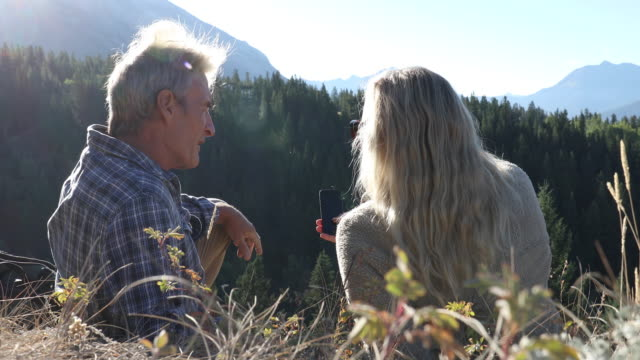 hiking couple relax on grassy summit, use smart phone - montagne rocciose video stock e b–roll