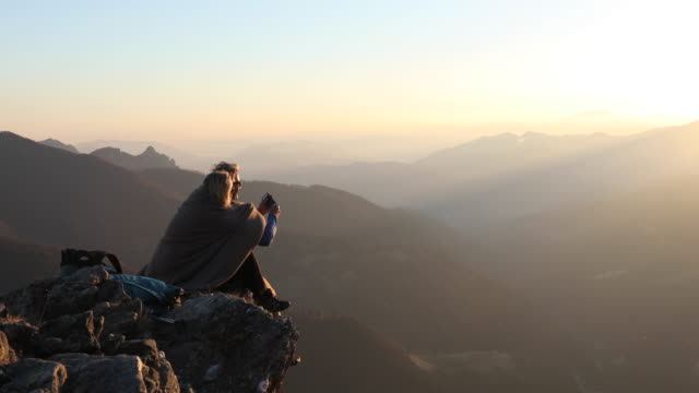 hiking couple relax on mountain summit, in blanket - erinnerung stock-videos und b-roll-filmmaterial