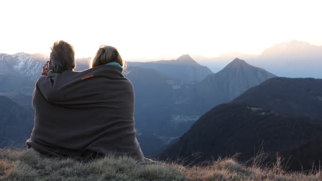 Hiking couple relax on mountain summit, in blanket
