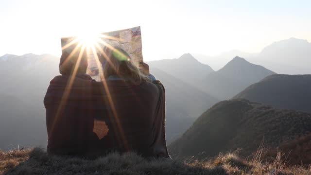 vidéos et rushes de hiking couple relax on mountain summit, in blanket - quinquagénaire