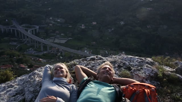 hiking couple relax on rock ledge, above highway, valley - achievement点の映像素材/bロール