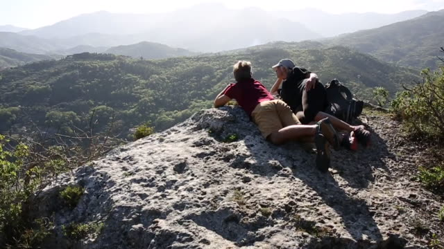 hiking couple relax on rock ledge, look out across valley - tal stock-videos und b-roll-filmmaterial