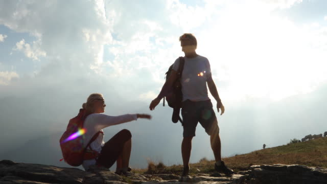 hiking couple relax on rocks, mountains in distance - assistance stock videos & royalty-free footage