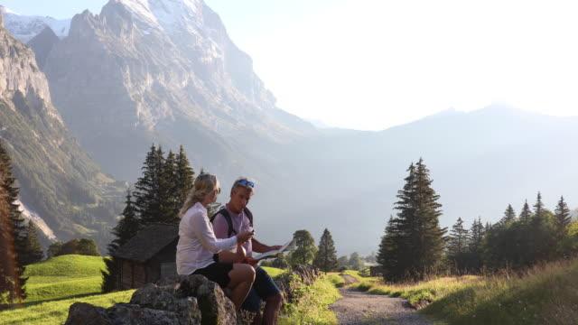 wanderpaar entspannen auf steinmauer, blick auf karte - entscheidung stock-videos und b-roll-filmmaterial