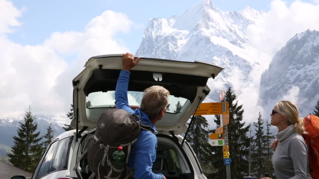 vídeos de stock e filmes b-roll de hiking couple remove gear from car, prepare to start hike - gola alta