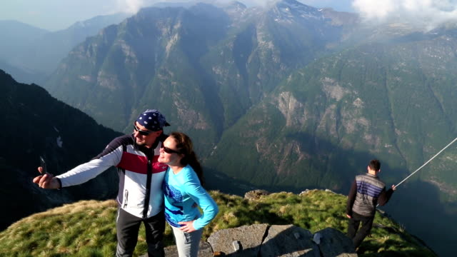Hiking couple take pictures from mountain summit, besides others
