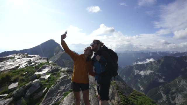hiking couple take selfie on top of mountain top - see other clips from this shoot 31 stock videos & royalty-free footage