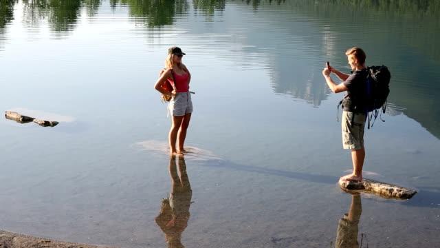 Hiking couple take smart phone pic, mountain pond