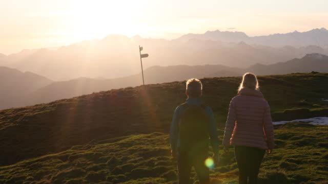 hiking couple traverse alpine meadow, read directional sign - achievement点の映像素材/bロール