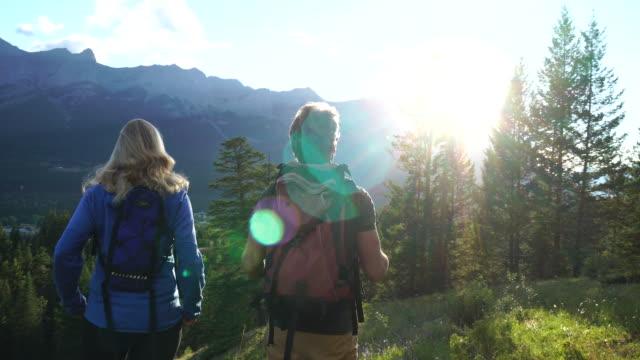 Hiking couple traverse alpine meadow, towards distant mountains