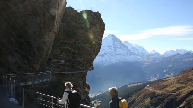 vídeos de stock e filmes b-roll de hiking couple walk along guarded pathway above mountain slope - cable