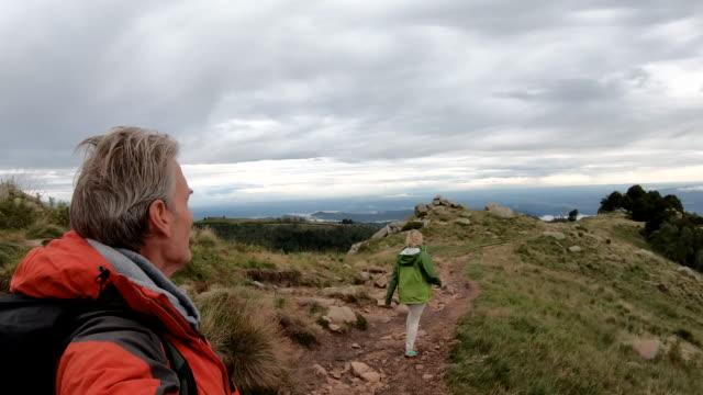 vidéos et rushes de promenade de couples de randonnée le long de la crête de pré - 55 59 ans