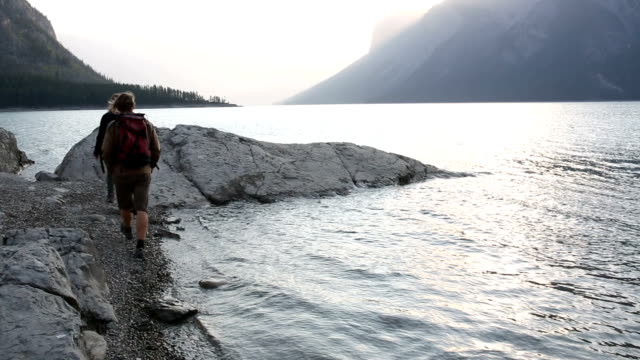 hiking couple walk along mountain lakeshore at sunrise - lakeshore stock videos and b-roll footage