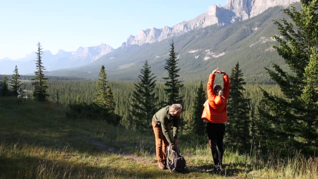 hiking couple walk along mountain trail, early morning - banff national park stock videos & royalty-free footage