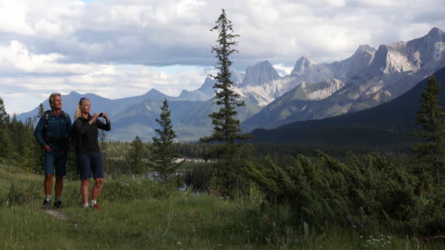 hiking couple walk along trail, past mountains - alberta stock videos & royalty-free footage