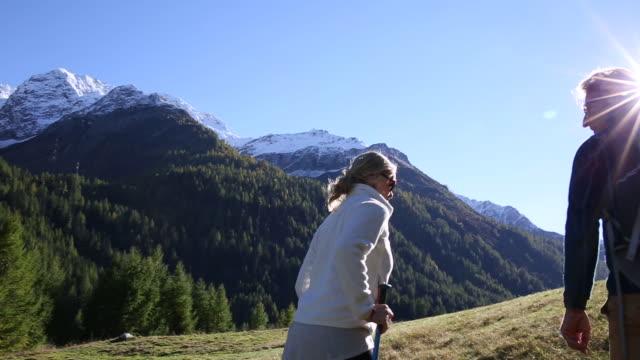 hiking couple walk into mountain meadow, towards sunrise - erholung stock-videos und b-roll-filmmaterial
