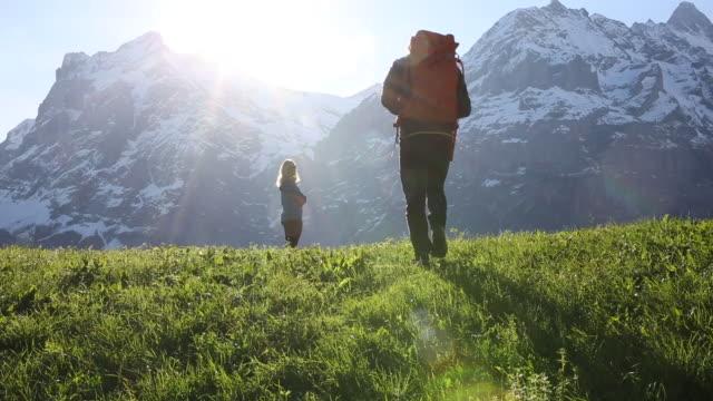 Hiking couple walk onto grassy mountain meadow, sunrise