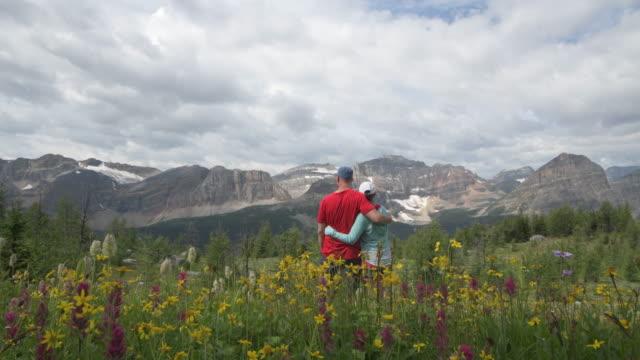 hiking couple walk past alpine wildflowers, mountains - alberta stock videos & royalty-free footage