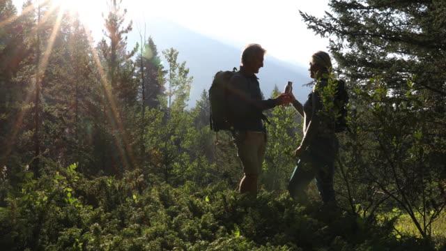vidéos et rushes de hiking couple walk through forest, in mountains - 55 59 ans