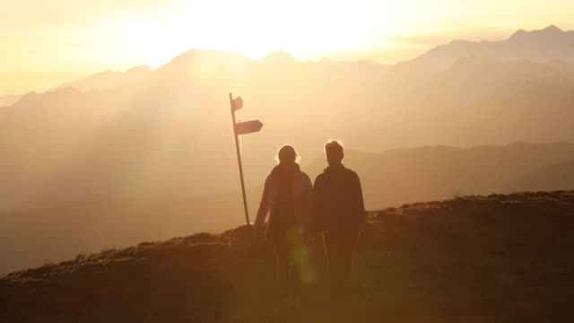hiking couple walk through mountain meadow - directional sign stock videos & royalty-free footage