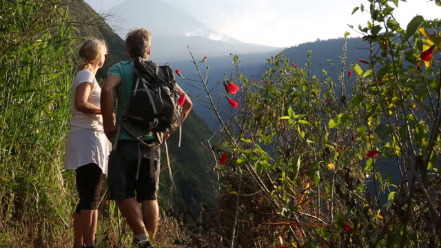 stockvideo's en b-roll-footage met hiking couple walk to edge of mountain path, volcano above - handen op de heupen