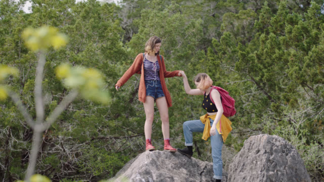 Hiking girl reaches out hand to help sister climb to the top of the mountain.