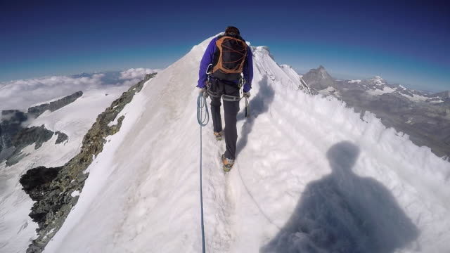 POV hiking icy mountain ridge