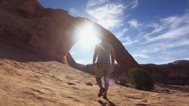 pov hiking in the colorado plateau: corona arch near moab - arch stock videos & royalty-free footage