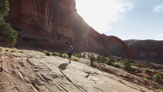 hiking in the colorado plateau: corona arch near moab - red rocks stock videos and b-roll footage