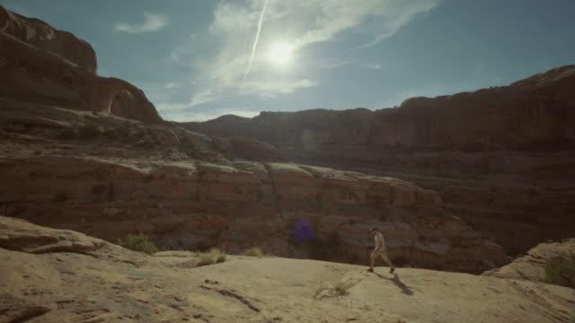 hiking in the colorado plateau: corona arch near moab - colorado plateau stock videos & royalty-free footage