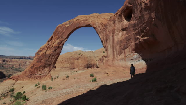 hiking in the colorado plateau: corona arch near moab - natural arch stock videos & royalty-free footage