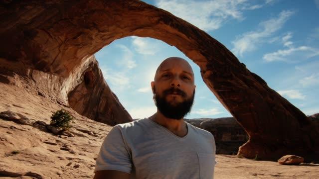 pov hiking in the colorado plateau: corona arch near moab - colorado plateau stock videos & royalty-free footage