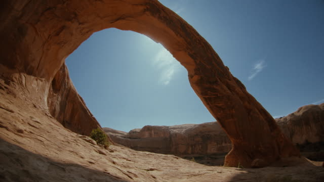 hiking in the desert: under corona arch, moab - arch stock videos & royalty-free footage
