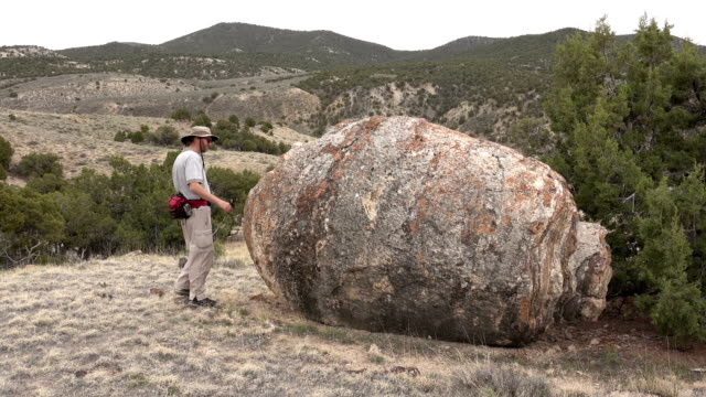 Hiking man explores ancient huge Ducey Stromatolite limestone fossil northwest Colorado