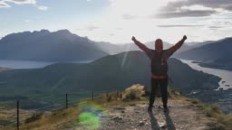 Hiking man standing on mount top success in sunny day